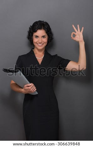 Beautiful businesswoman showing okay sign and smiling for the camera. Lady with black hair holding documents in her hand over grey. - stock photo
