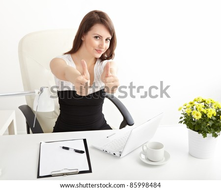 Beautiful  businesswoman  shows thumb  in brightly lit office and smiling