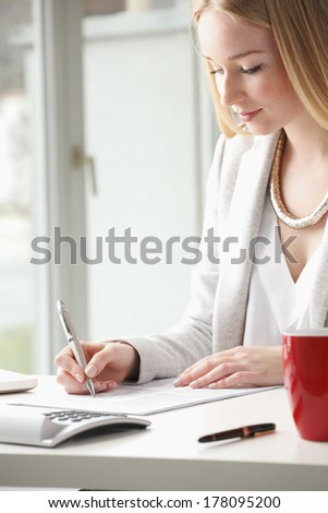 Beautiful businesswoman sitting at desk and fill the form. - stock photo