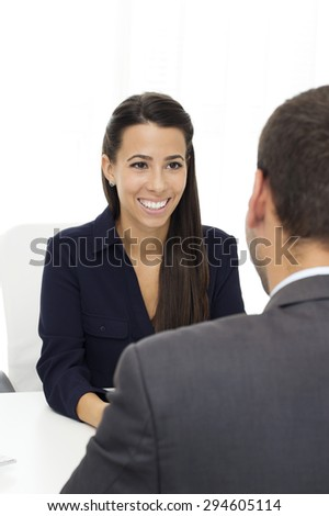 Beautiful  businesswoman sitting at the desk face to face with male client and talking in the office. - stock photo