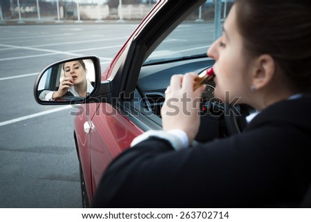 Beautiful businesswoman sitting in car and applying lipstick