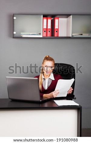 beautiful businesswoman sitting in office and reading paper. looking at camera - stock photo