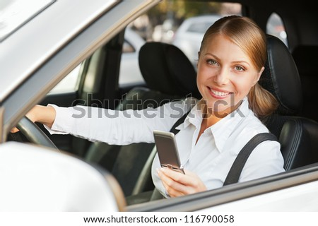 beautiful businesswoman sitting in the car and holding mobile phone - stock photo