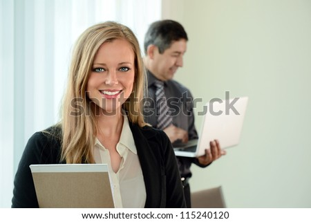 Beautiful businesswoman smiling with coworker in background