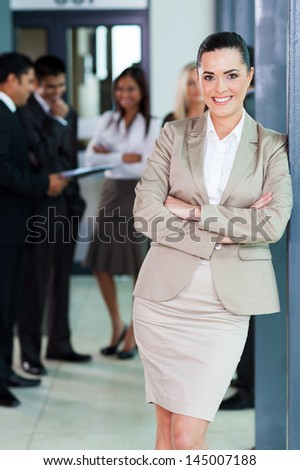 beautiful businesswoman standing in office with colleagues on background - stock photo