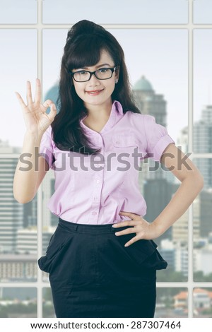 Beautiful businesswoman standing in the office and showing okay sign near the window - stock photo