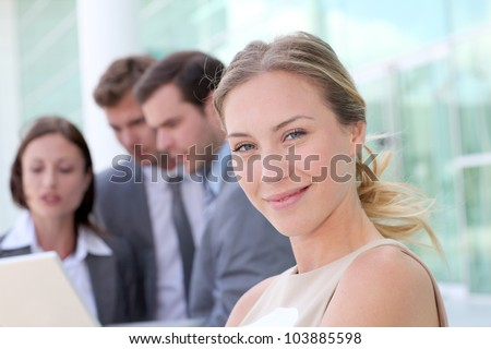 Beautiful businesswoman standing outside in front of team - stock photo