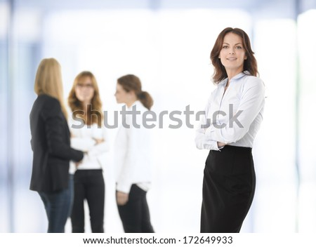 Beautiful businesswoman standing, people in  the background.