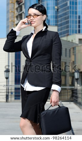 Beautiful businesswoman talking cellphone, outdoor shoot - stock photo