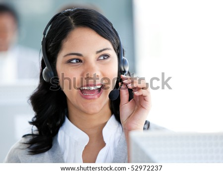 Beautiful businesswoman talking with clients in front of her computer in the office - stock photo