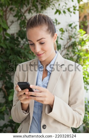 Beautiful businesswoman texting on phone on a sunny day