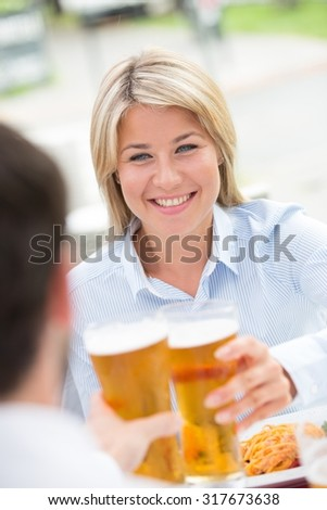 Beautiful businesswoman toasting beer glass with male colleague at restaurant - stock photo