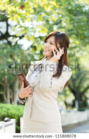 Beautiful businesswoman using a cellular phone. Portrait of asian. - stock photo