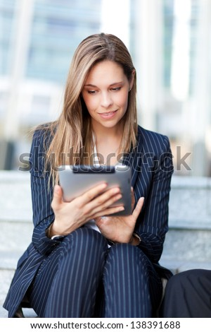 Beautiful businesswoman using a tablet outdoor in the city - stock photo