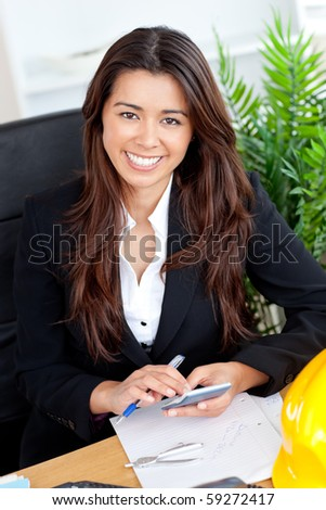 Beautiful businesswoman using calculator smiling at the camera in her office - stock photo