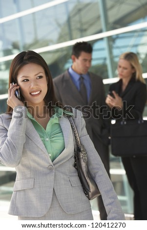 Beautiful businesswoman using cell phone with colleagues in background - stock photo