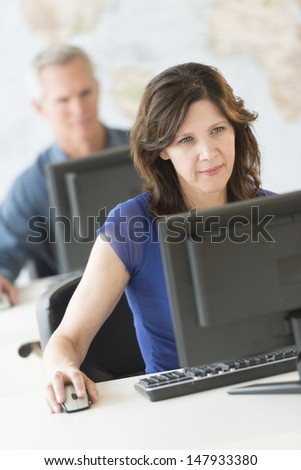 Beautiful businesswoman using computer with colleague working in background at office - stock photo