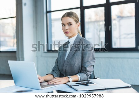 beautiful businesswoman using laptop in office and looking at camera