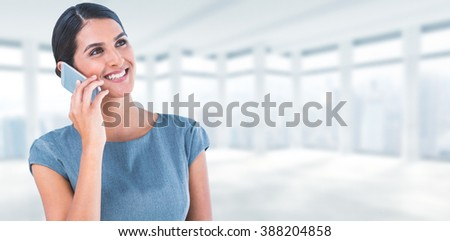 Beautiful businesswoman using mobile phone against windows overlooking city