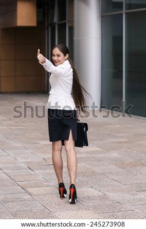 Beautiful businesswoman walk away and show thumb up - stock photo