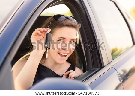 Beautiful businesswoman with carkey in her car