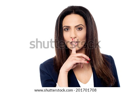 Beautiful businesswoman with finger on lips, shhh!! - stock photo