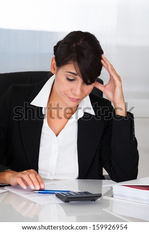 Beautiful Businesswoman With Headache Doing Calculation In Office