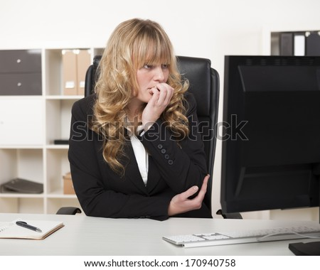 Beautiful businesswoman with long blond hair sitting at her desk reading her computer monitor with an intent expression - stock photo