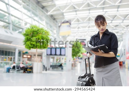 Beautiful businesswoman with luggage reading book in an airport - stock photo
