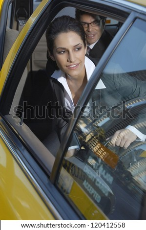 Beautiful businesswoman with male colleague getting out of taxi - stock photo