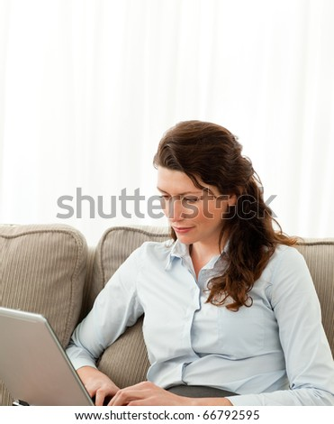 Beautiful businesswoman working on her laptop on the sofa at home