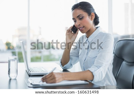 Beautiful businesswoman working sitting at her desk in the office - stock photo