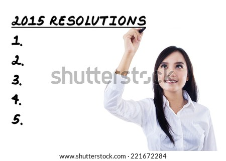 Beautiful businesswoman writes resolutions list in 2015 - stock photo