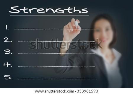 Beautiful businesswoman writing list of business strength  - stock photo