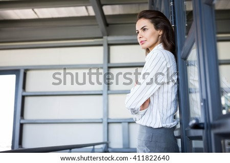 Beautiful businesswoman young leaning on office door - stock photo
