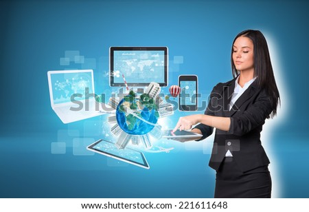 Beautiful businesswomen in suit using digital tablet. Earth with buildings and laptop, tablets and smartphone. Element of this image furnished by NASA - stock photo