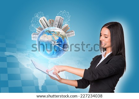 Beautiful businesswomen in suit using digital tablet. Earth with buildings. World map and chessboard as backdrop. Element of this image furnished by NASA - stock photo