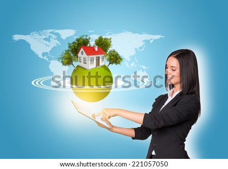 Beautiful businesswomen in suit using digital tablet. Earth with house and trees. World map as backdrop - stock photo