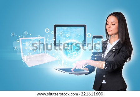 Beautiful businesswomen in suit using digital tablet. Earth with laptop, tablets and smartphone. Element of this image furnished by NASA - stock photo