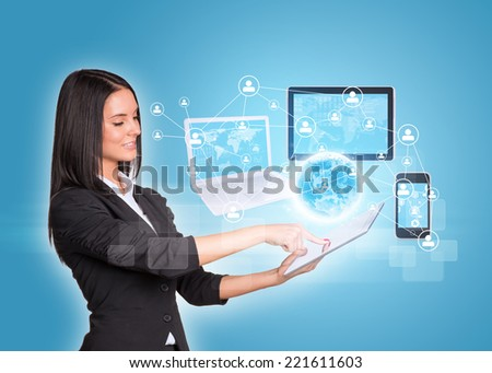 Beautiful businesswomen in suit using digital tablet. Earth with laptop, tablets and smartphone. Element of this image furnished by NASA