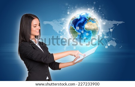 Beautiful businesswomen in suit using digital tablet. Earth with network and world map. Element of this image furnished by NASA - stock photo