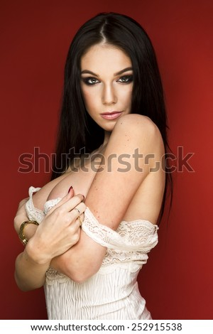 Beautiful busty brunette in a sexy white white lingerie posing against a red studio background - stock photo