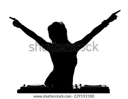 Beautiful busty DJ with her headphones is standing at her deck mixing sound. - stock photo