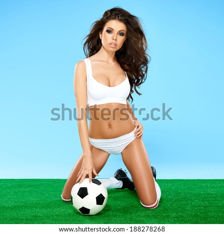 Beautiful busty female soccer player in white sport lingerie and boots kneeling on a green and blue background with a soccer ball giving the camera a sultry seductive look