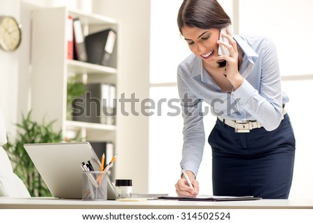 Beautiful Busy Businesswoman, standing in office, writing in planner and talking on mobile phone. - stock photo