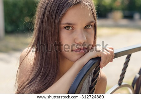 beautiful but sad girl sitting on a bench in the Park - stock photo