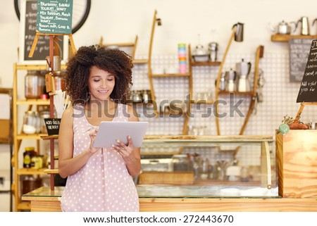 Beautiful cafe owner running her small business with the help of a digital tablet while standing near the counter of her coffee shop - stock photo