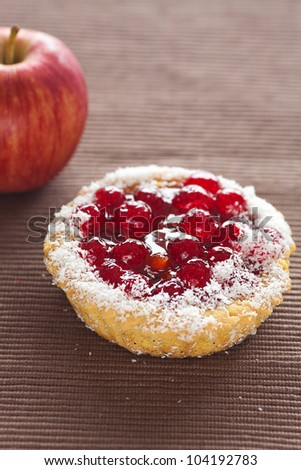 beautiful cake with berries and apple on brown mat