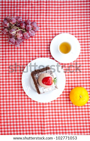 beautiful cake with strawberry,fruits and tea on plaid fabric