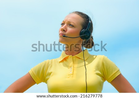 Beautiful call centre operator or client services office trying to explain something to a client over the microphone of her headset  - stock photo